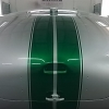 A green and silver car hood being spray painted with automotive spray paint in the DIY spray booth.